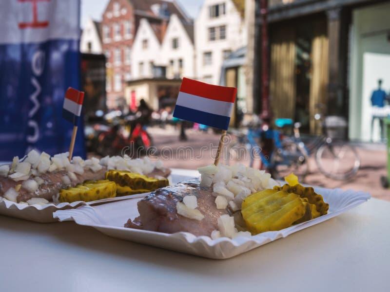 Traditionelles niederländisches Straßenlebensmittel - frischer Hering mit Zwiebeln und Essiggurken stockfotografie