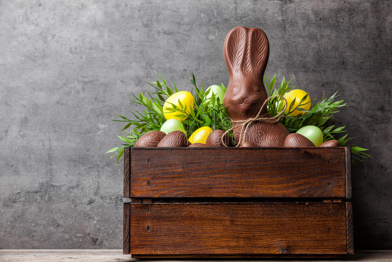 Traditionelles Ostern-Schokoladenhäschen und -eier innerhalb einer hölzernen Kiste stockfotografie