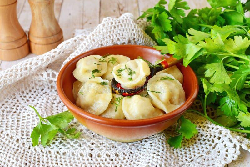 Traditionelles russisches pelmeni mit dem Hackfleisch und Zwiebeln, die eine braune keramische Schüssel ausfüllen lizenzfreies stockfoto