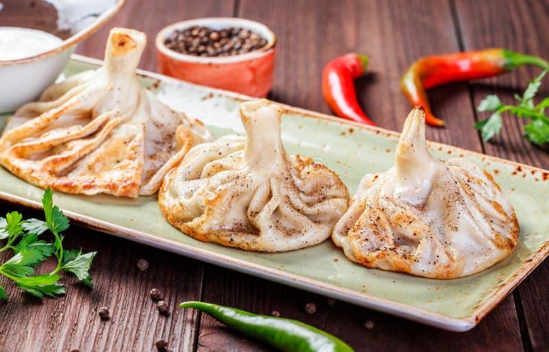 Traditionelles russisches pelmeni, Ravioli, Mehlklöße mit Fleisch in der Platte auf hölzernem Hintergrund Petersilie, Sauerrahm u stockbilder