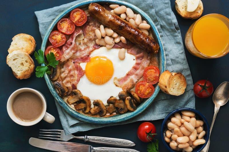 Traditionelles Spiegelei des englischen Frühstücks mit Wurst, Pilzen, Bohnen, Tomaten und Speck Ansicht von oben Toast mit Butter stockbilder