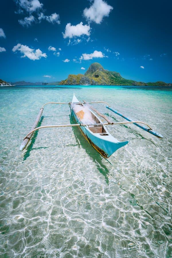 Traditionellt fartyg för filippinofisherbanca i den blåa lagun på fjärden för El Nido med den Cadlao ön på bakgrund Palawan ? royaltyfria foton