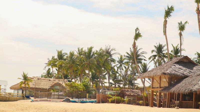 Traditionellt fiskeläge bland palmträd på den sandiga kustFilippinerna royaltyfri foto