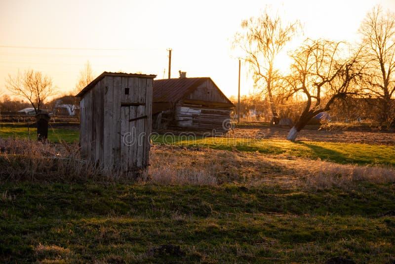 Traditionellt gammalt träWC-uthus i trädgården i sommar royaltyfri fotografi
