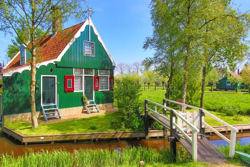 Traditionellt grönt holländskt hus med den lilla träbron mot blå himmel i den Zaanse Schans byn, Nederländerna Berömd turism royaltyfria bilder