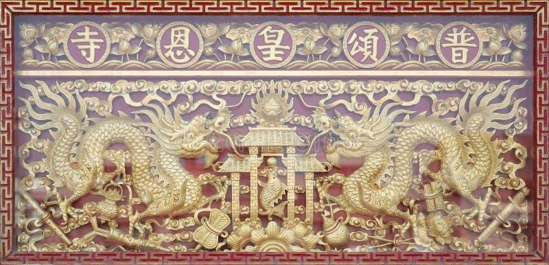 Traditionellt guld- kinesiskt draketr? som snidas med spegeln, reflekterar arkivfoto