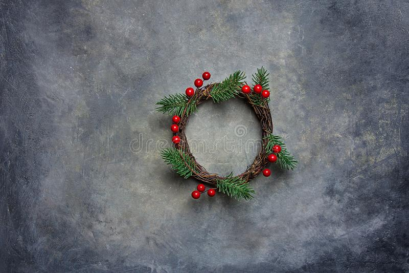 Traditionellt handgjort ris Holly Berries för filialer för träd för gran för julkransgräsplan på Grungy mörk stenbakgrund Top bes royaltyfri bild