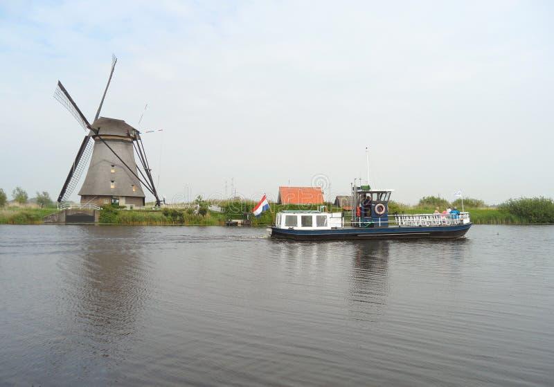 Traditionellt holländskt väderkvarn och fartyg på kanalen på Kinderdijk royaltyfri bild