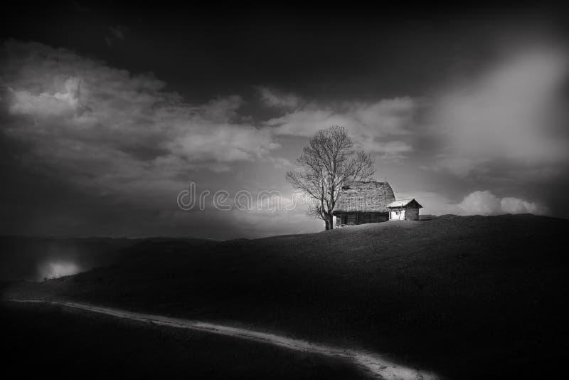 Traditionellt hus över en kulle, svartvit bild arkivbilder