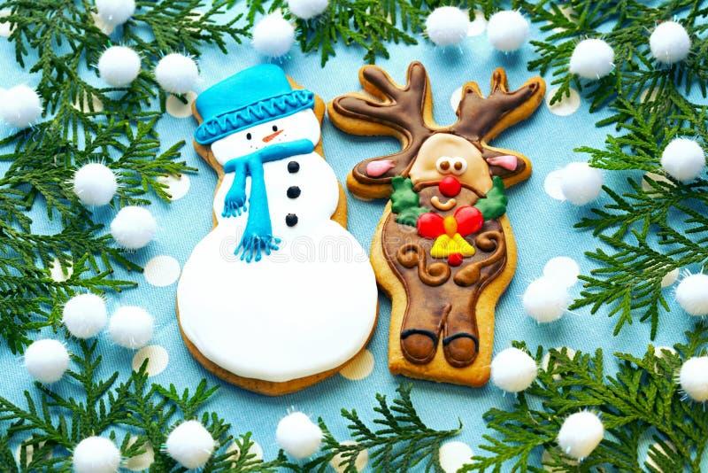 Traditionellt, jul, ljust rödbrun pepparkakor, kakor en hjort och ett snögubbeslut upp på en blå bakgrund med gran-träd filialer arkivfoto