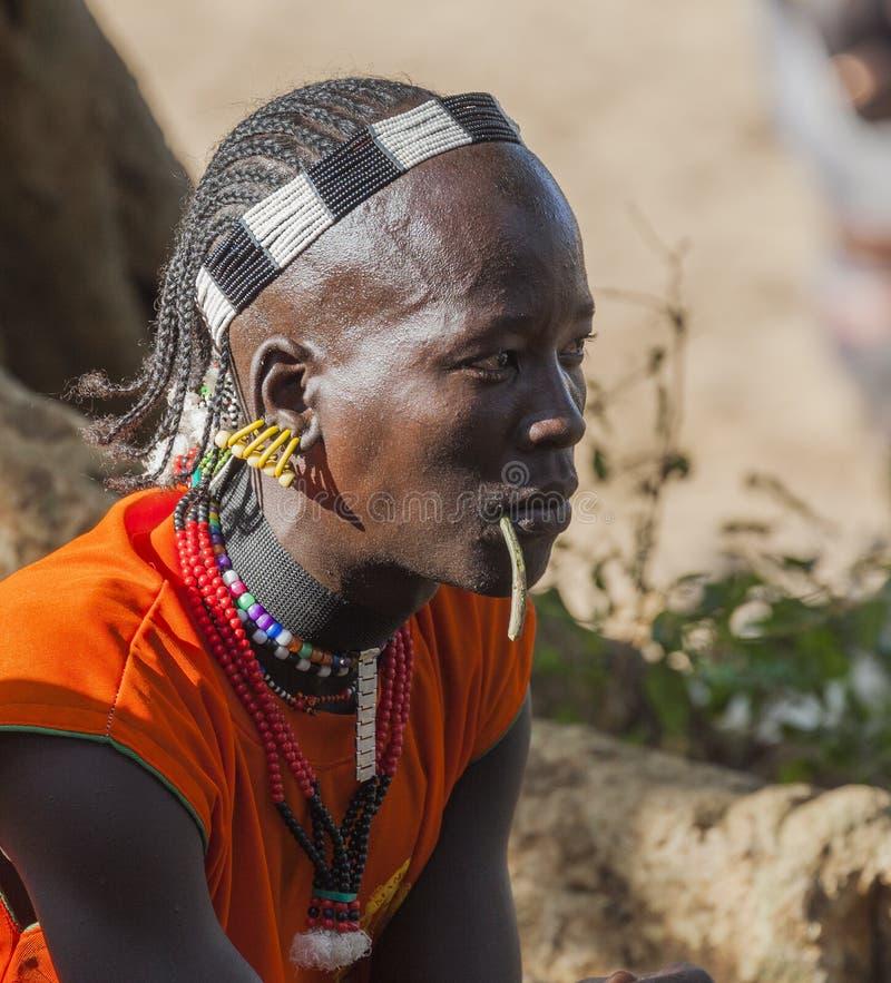 Traditionellt klädd Hamar man med att tugga pinnen i hans mun Turmi Omo dal, Etiopien arkivfoto