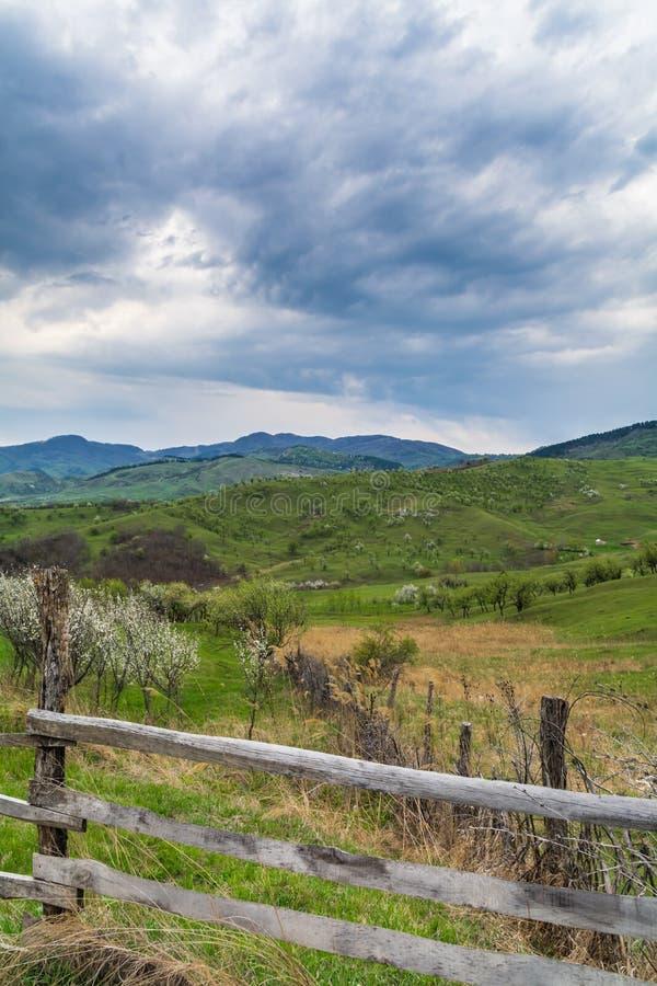Traditionellt landskap för gröna kullar över molnig himmel på bakgrund Fotvandrareparadis i bygden Rumänien royaltyfri bild