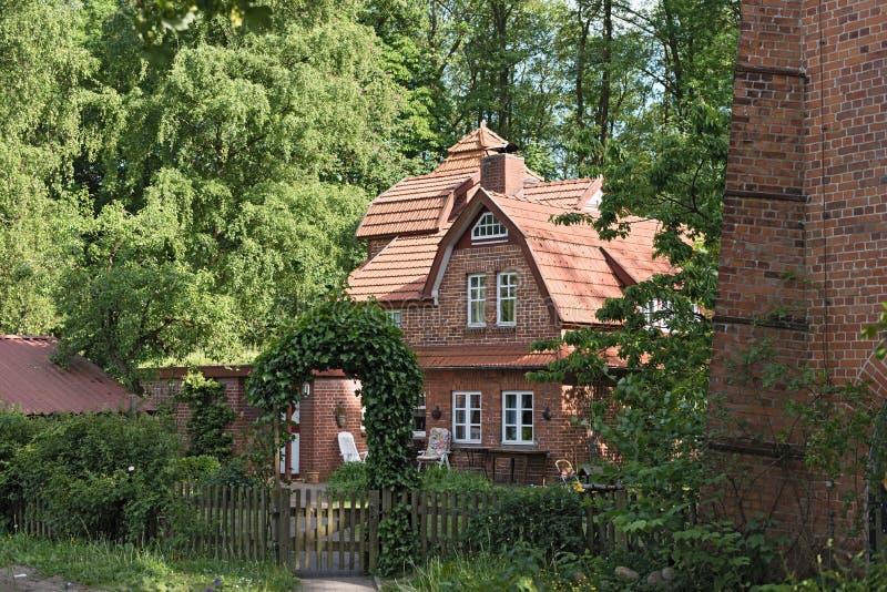 Traditionellt lantbrukarhem för röd tegelsten i norden av Hamburg, Tyskland fotografering för bildbyråer