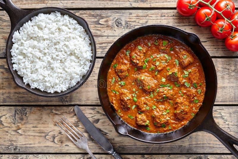 Traditionellt Madras smörnötkött saktar mat för kött för lammet för den kockIndian kryddig chili med ris arkivbilder