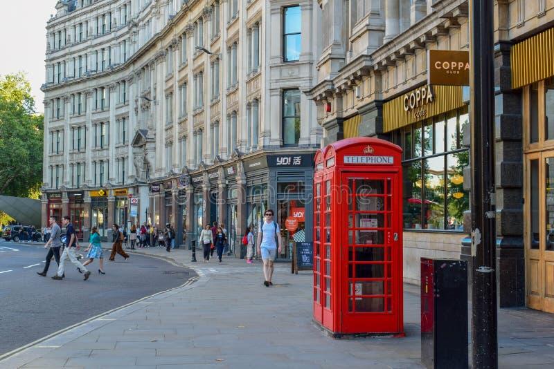 Traditionellt rött telefonbås i den London gatan arkivbild