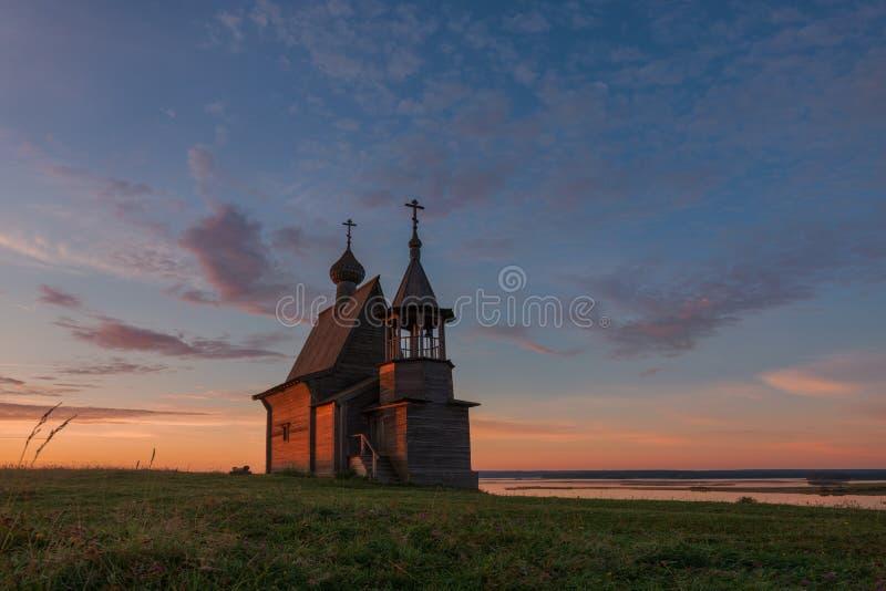Traditionellt ryskt ortodoxt träkyrkligt kapell av StNicholas på överkanten av kullen i den Vershinino byn på soluppgång norr arkivfoton