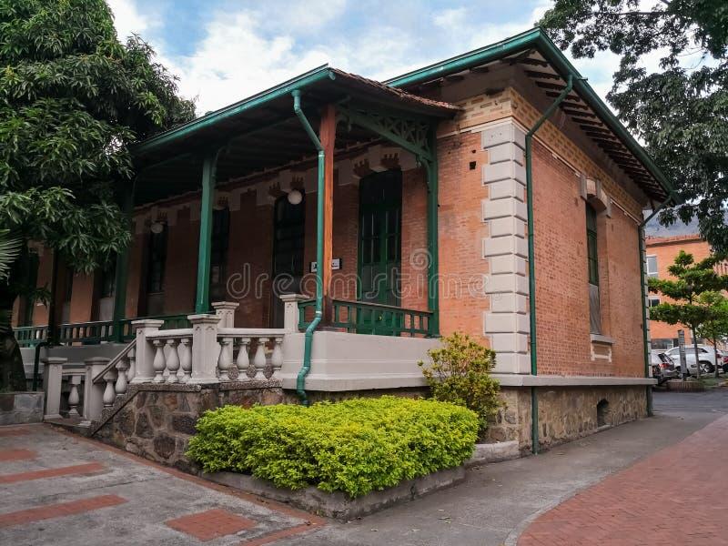 Traditionellt spanskt kolonialt hus med gröna träkolonner och den stora farstubron royaltyfria bilder