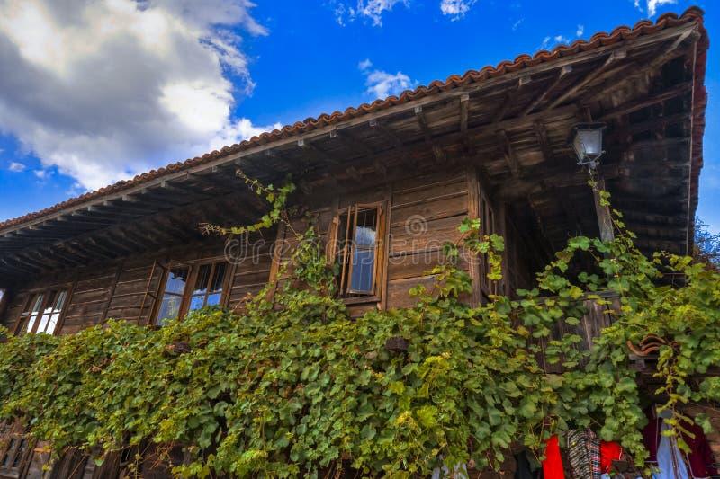 Traditionellt trähus med vinrankan i Zheravna Jeravna, Bulgarien, Europa royaltyfri fotografi
