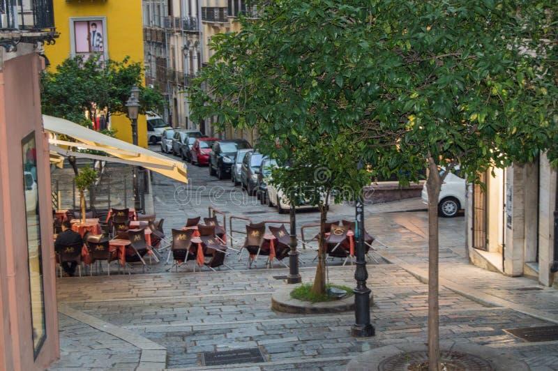 Traditionellt utomhus- kafé på en smal lappad gata efter regn i Cagliari, Italien, 09 Oktober 2018, SELEKTIV FOKUS arkivbild