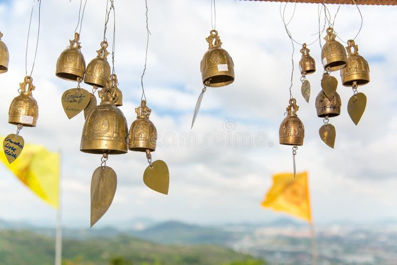 Traditionsasiatet sätter en klocka på i buddismtempel i den Phuket ön, Thailand Berömda stora Buddhaönskaklockor arkivbild