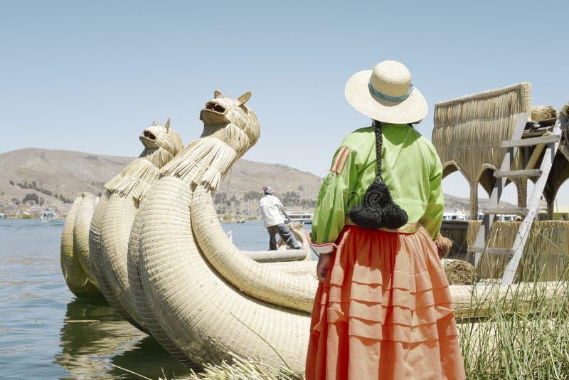 Traditionsgemäß gekleidete Aymara-Frau, die den Schiffer erreicht in Richtung zu ihr, Uros Floating Islands, See Titi betrachtet stockfotos