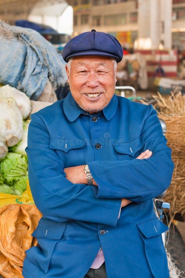 Traditionsgemäß gekleideter Landwirt auf einem Markt, Weihai, China lizenzfreie stockfotografie