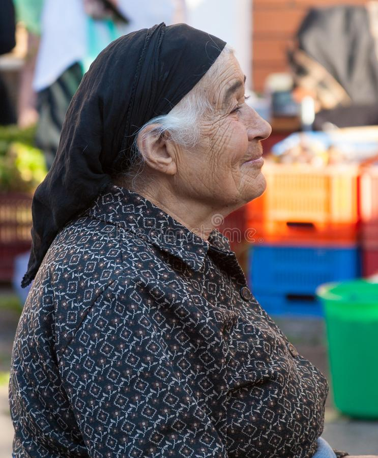 Traditionsgemäß gekleideter Verkauf von landwirtschaftlichen Erzeugnissen der alten Frau ihr Erzeugnis am Th lizenzfreies stockbild
