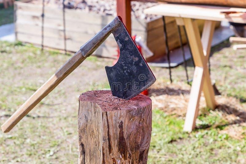 Traditionsvikingvapen slåss det breda bladet för yxan som den svarta trähandtagfyrkanten klibbade den gamla stubben arkivbild
