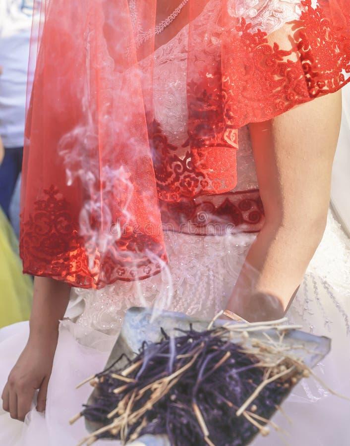 Tradizione di Shamanic per buona fortuna in Turchia rurale L'incenso dei bastoni dell'erba fuma va alle giovani coppie in una cer fotografia stock