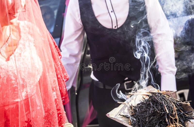 Tradizione di Shamanic per buona fortuna in Turchia rurale L'incenso dei bastoni dell'erba fuma va alle giovani coppie in una cer immagine stock libera da diritti