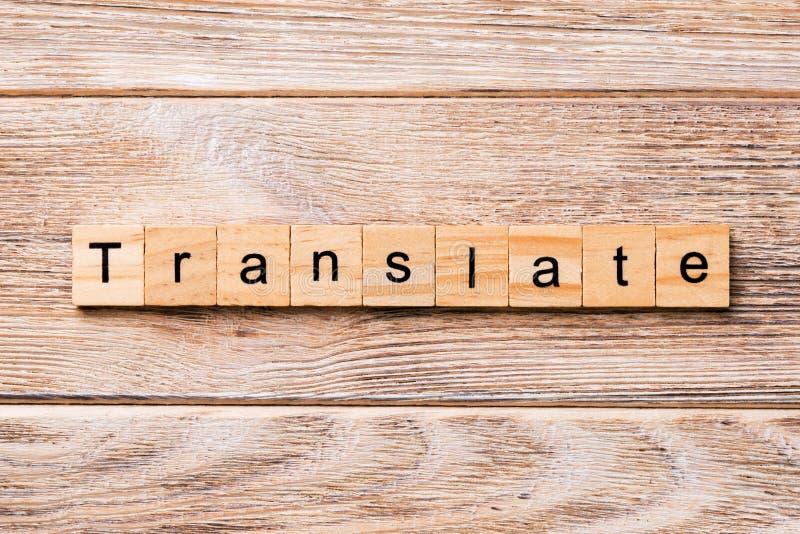 Traduca la parola scritta sul blocco di legno Traduca il testo sulla tavola di legno per vostro desing, concetto immagini stock