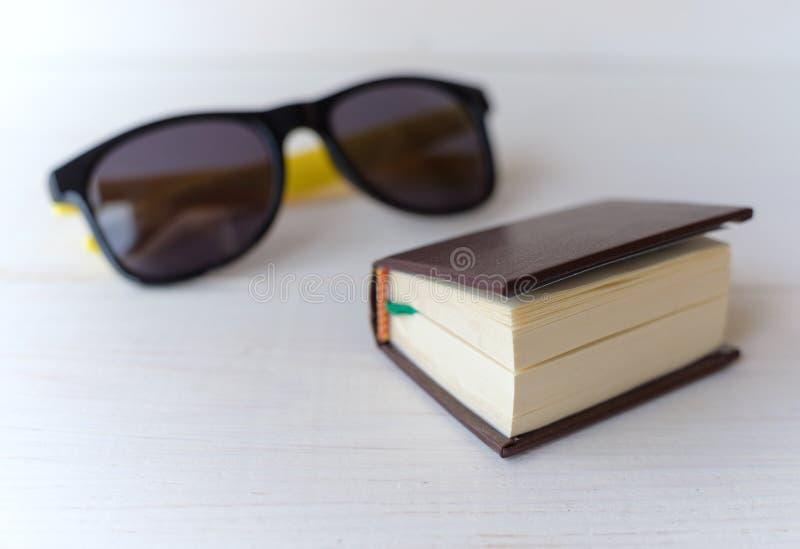Tradutor e óculos de sol do livro de bolso foto de stock royalty free