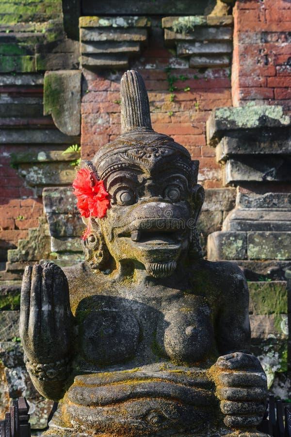 Tradycyjna Bali wyspy kamienia rzeźba naga kobieta i dekorująca z lokalnym czerwonym kwiatu okwitnięciem fotografia royalty free