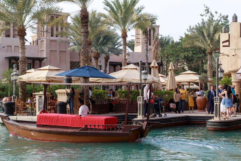 Tradycyjna drewniana arabska łódź unosi się przeciw tłu chodzący turyści w Madinat Jumeirah obraz stock