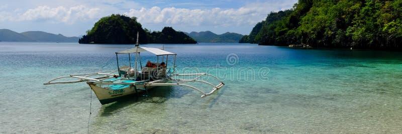 Tradycyjna drewniana filipińska łódź w błękitnej lagunie fotografia stock