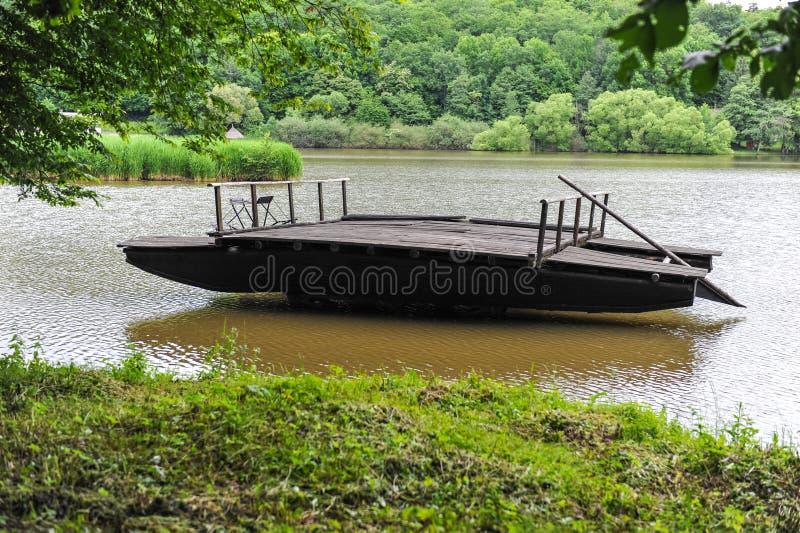 Tradycyjna drewniana tratwa unosi się na jeziorze obrazy royalty free