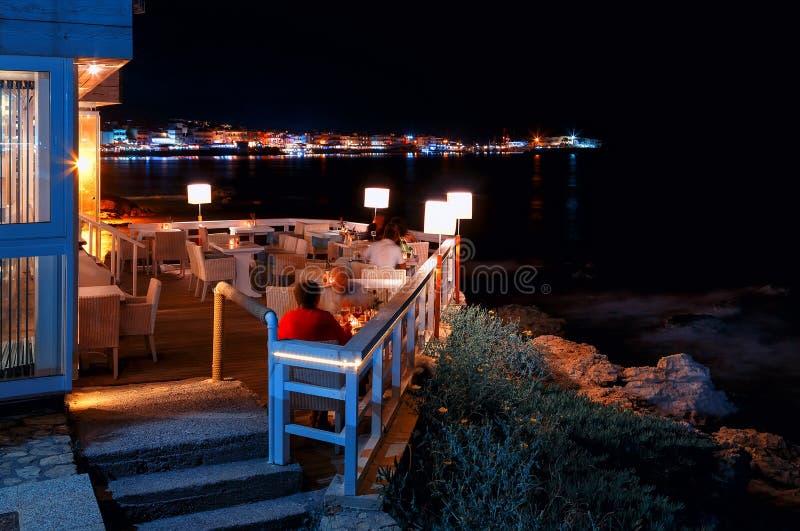 Tradycyjna grecka kawiarnia z ludźmi łozinowego meble na plaży z noc widokami zatoka i port Hersonissos zdjęcia royalty free