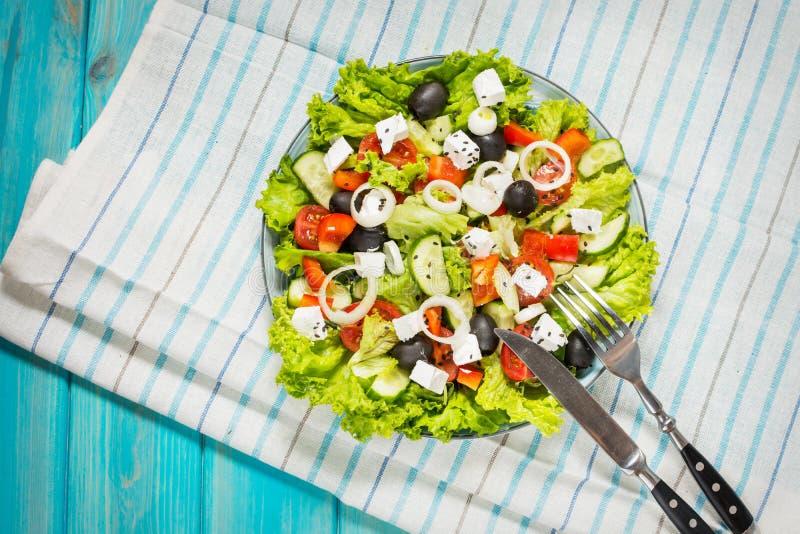 Tradycyjna grecka sałatka z świeżymi warzywami, feta serem i oliwkami na błękitnym drewnianym tle, zdjęcia stock