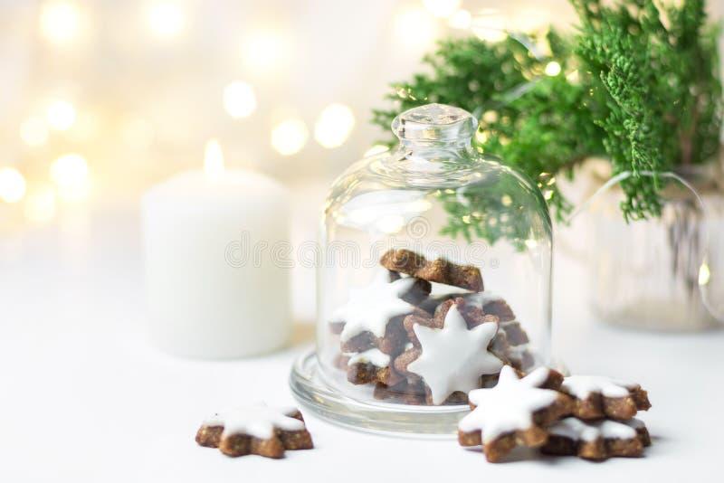 Tradycyjna gwiazda kształtujący niemiec cynamonowi ciastka z lodowaceniem w cloche kopuły dzwonkowym szkle zgrzytają na bielu sto fotografia royalty free