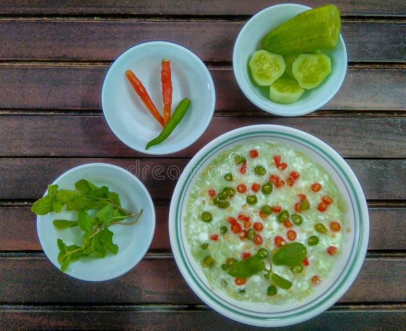 Tradycyjna Indiańska kuchnia Domowej roboty ogórkowy raita z jogurtem, solą, mennicą, chilies i pikantność na drewnianym tle, Gre fotografia stock