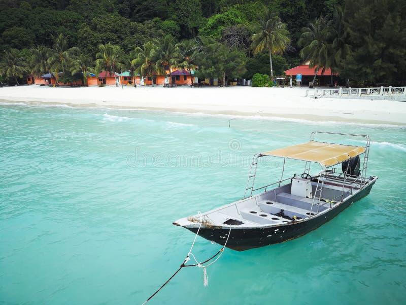 Tradycyjna longtail łódź unosi się w jasnej wodzie na wyspa raju Pulau Redang, Malezja fotografia royalty free