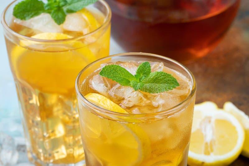 Tradycyjna lukrowa herbata z cytryną, mennicą i lodem w wysokich szkłach, Dwa szkła z chłodno latem piją na starym ośniedziałym t fotografia stock