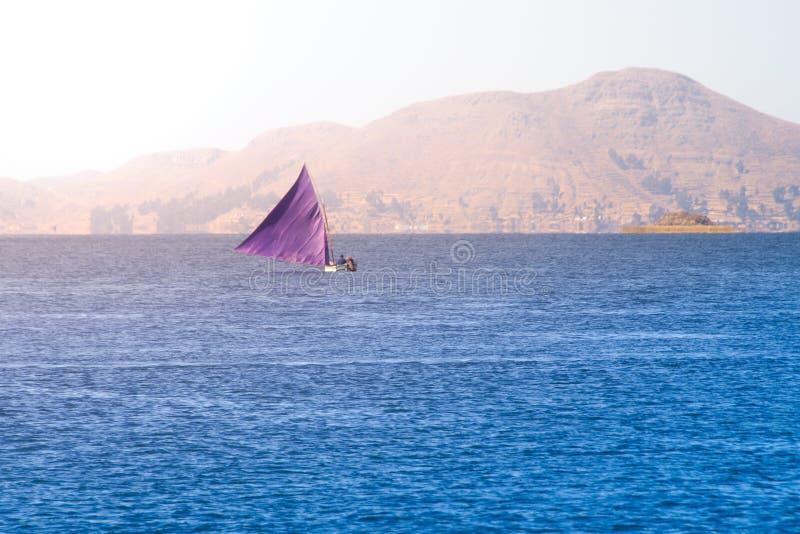 Tradycyjna mała żeglowanie łódź z trójboka fiołkowym żaglem na Titicaca jeziorze, Peru i Boliwia, Ameryka Południowa zdjęcia royalty free