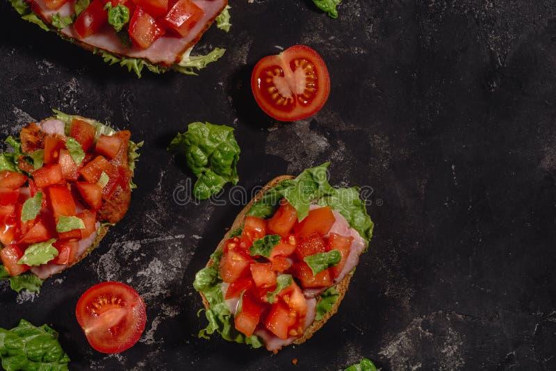 Tradycyjna w?oszczyzna Bruschetta z pomidorami, mozzarella kumberlandem, sa?atka li??mi i baleronem na ciemnym batuty tle siekaj? fotografia royalty free