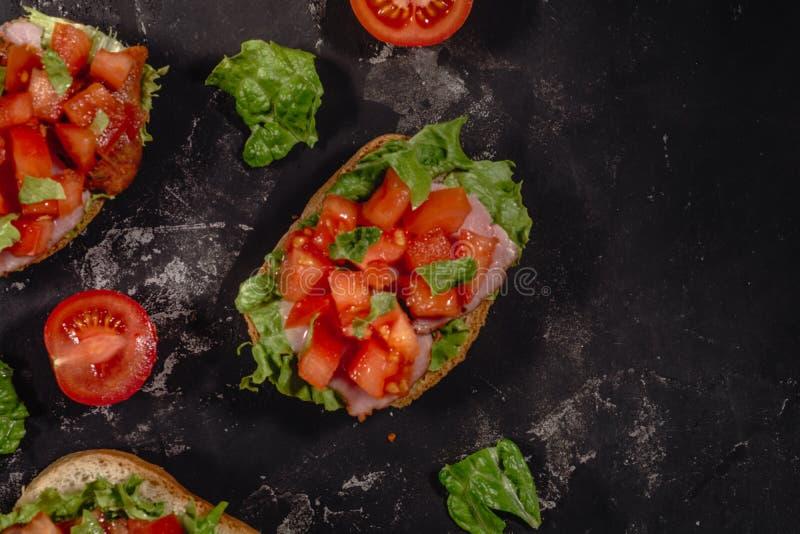 Tradycyjna w?oszczyzna Bruschetta z pomidorami, mozzarella kumberlandem, sa?atka li??mi i baleronem na ciemnym batuty tle siekaj? zdjęcie royalty free