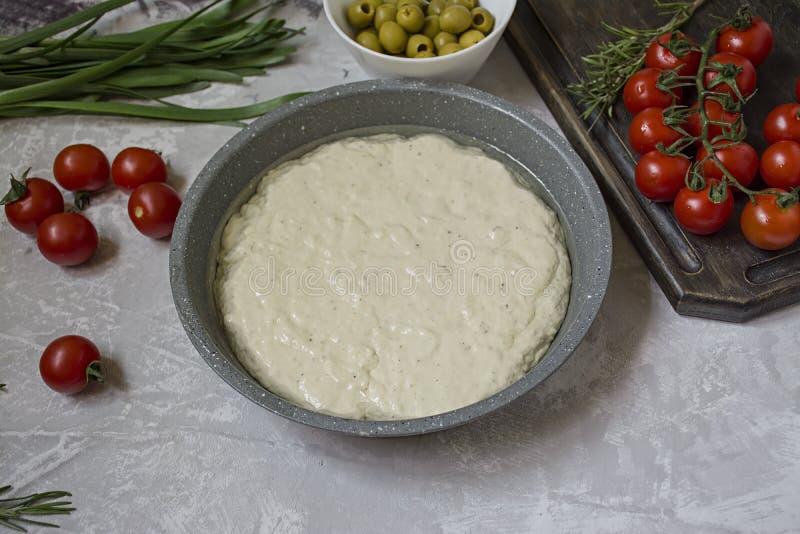 Tradycyjna w?oszczyzna Focaccia z pomidorami, oliwkami i rozmarynami, Focaccia kulinarny proces, sk?adniki Focaccia ciasto fotografia royalty free