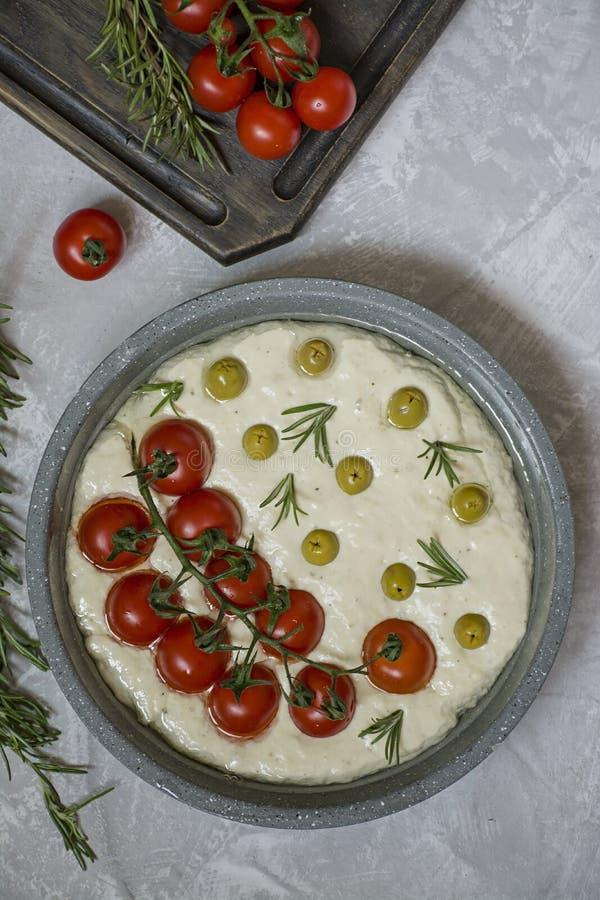 Tradycyjna w?oszczyzna Focaccia z pomidorami, oliwkami i rozmarynami, Focaccia kulinarny proces, sk?adniki Focaccia ciasto obraz stock