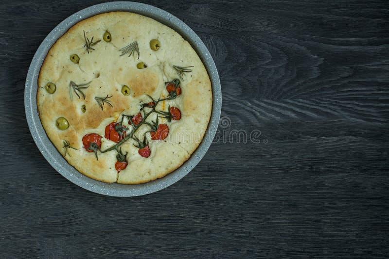Tradycyjna w?oszczyzna Focaccia z pomidorami, oliwkami i rozmarynami, Piec focaccia w wypiekowej tacy Round forma Proces zdjęcie royalty free
