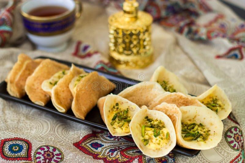 Tradycyjne Arabskie kataif krepy faszerować z śmietanką i pistacjami przygotowywającymi dla iftar w Ramadan na Paisley tle, obrazy stock