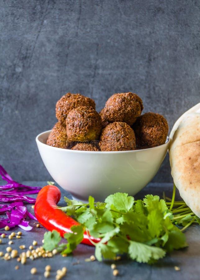 Tradycyjne domowej roboty chickpea Falafel piłki w pucharze z kolenderami opuszczają & ziarna, czerwony pieprz & kapusta, pitta c obrazy stock